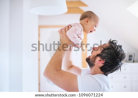 Father with a toddler girl in bedroom at home, having fun.