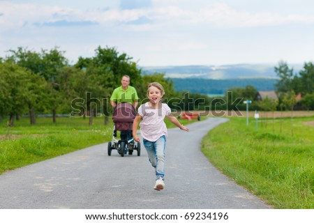 Father with child and a baby lying in a baby buggy walking down a path outdoors