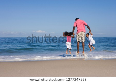 Father with children jumping in Atlantic surf on sandy beach vacation