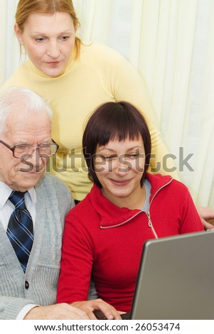Father with daughter and granddaughter in front of a laptop