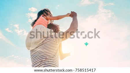 Father with daughter playing with kite and having fun on the beach - Dad enjoying time with his kid outdoor - Family relationship and love concept - Focus child body - Sunset colors tones filter #758515417