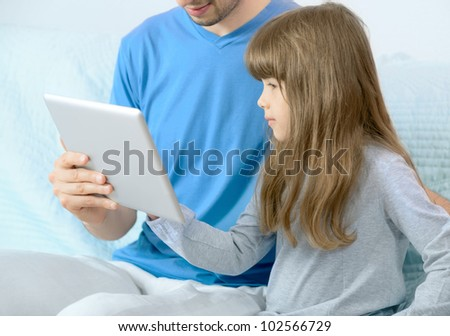 Father with daughter using digital tablet for fun. Selective focus on the child's face.