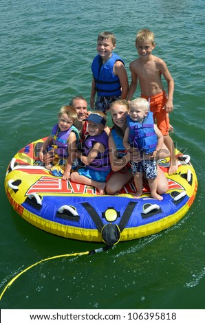 father with his kids on a tube on a lake