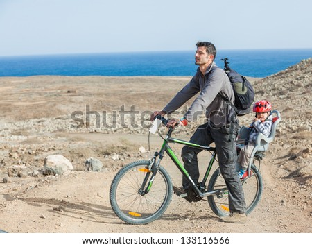 Father with his son having a weekend excursion on bike on a summer day in beautiful landscape