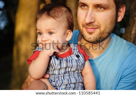 Father with his son in a park at sunset.