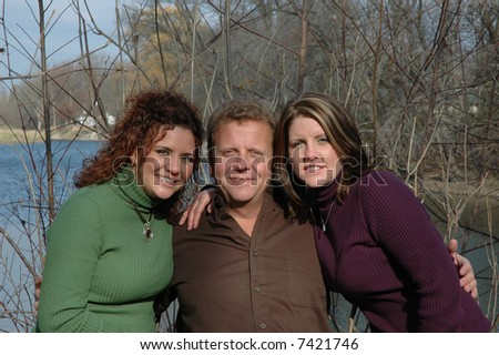father with his two grown daughters - stock photo