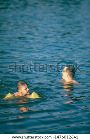 father with kid having fun in water swimming together summer vacation