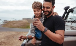 Father with little boy using smart phone together during road trip. Young boy with his father sitting at the front of the car.
