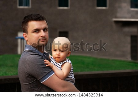 Father with one year old baby in his arms. Walk in an urban environment. The concept of urbanization and life in the city. The development of emotional intelligence. Early development