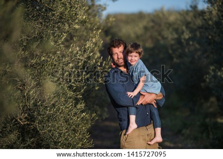 Father with small daughter standing outdoors by olive tree. #1415727095
