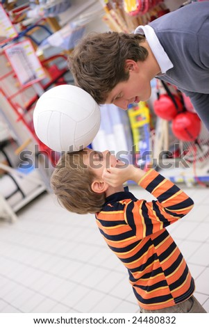 Father with son and ball in shop