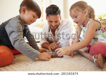 Father with son and daughter sitting on floor using digital tablet indoors. Happy young family together at home using touchpad computer. Young man teaching his children how to use digital tablet.