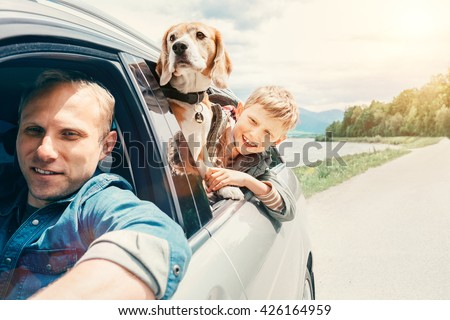 Father with son and dog look from the car window