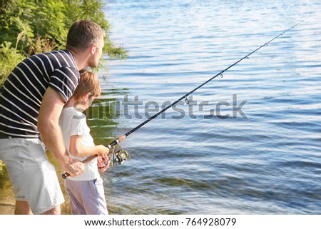 Father with son fishing from riverside