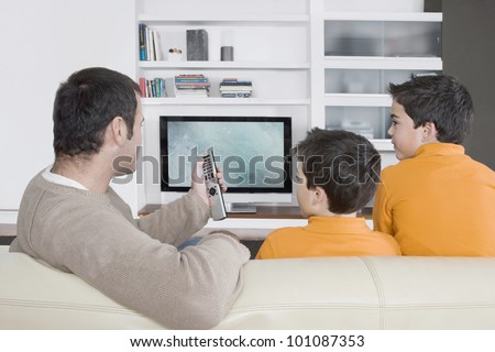 Father with twin brothers watching tv at home, using the control remote.