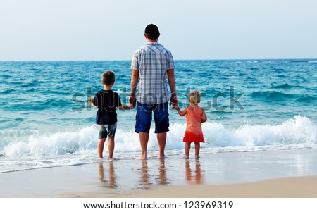 father with two kids on vacation at sea