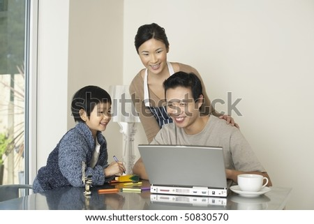 Father working on computer at dining room table, wife and son watching