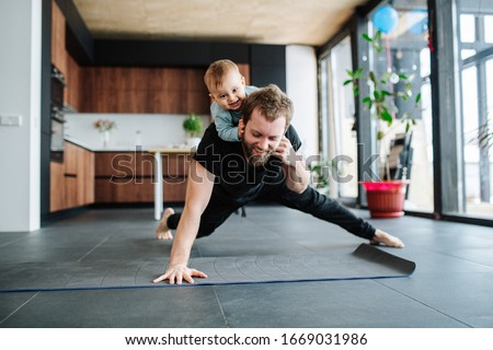 Father working out, doing single arm plank with his jolly infant baby riding on his neck. At home apartment.