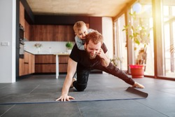 Father working out, doing single arm plank with his jolly infant baby riding on his neck. Stay at home apartment. Family quarantine, domestic life in self-isolation. Sunset light