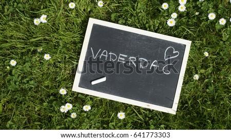 Fatherday written in Dutch on a chalkboard in a park between flowers                    #641773303