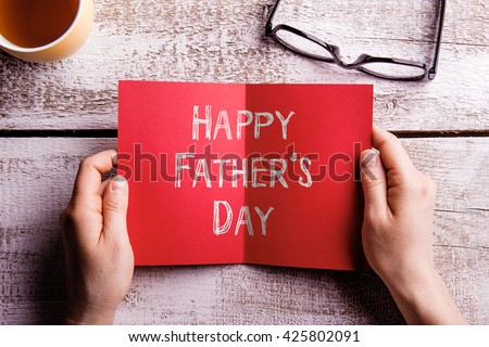 Fathers day composition. Hands of dad holding greeting card. Fathers day. Concept for fathers day celebration. Best father. Child and father concept. Happy fathers day text. #425802091