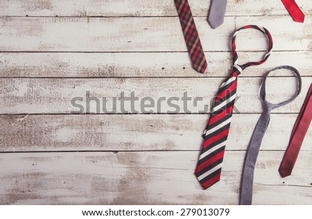 Fathers day composition of various colorful ties laid on wooden floor backround.
