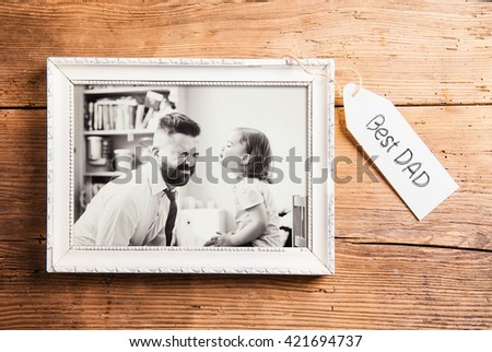 Fathers day composition. Picture frame. Wooden background. Young father enjoying time with child. Fathers day with daughter at home. Handsome father with little girl. Happy father and daughter.