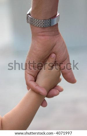 fathers hand holding little child\'s hand