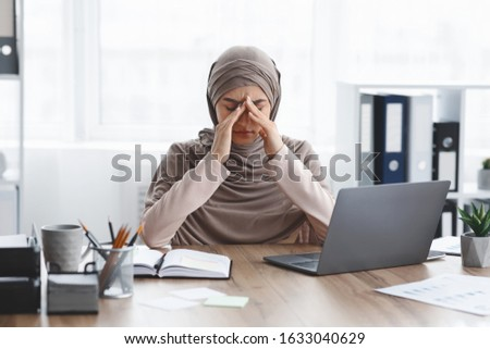 Fatigue Concept. Exhausted muslim busineswoman sitting at desk and touching her nose bridge, suffering from migraine and overworking in office
