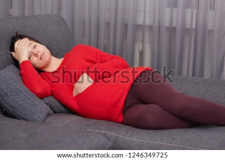 Fatigue European young woman keeps one hand on stomach and other on forehead, lies on comfortable sofa, rests at home, needs good rest, suffers from headache. Motherhood and tiredness concept #1246349725