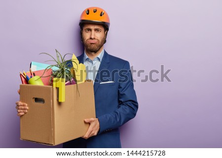 Fatigue male worker carries heavy cardboard box with office stuff, moves in new cabinet, wears helmet and suit, has dissatisfied tired facial expression, busy carrying paper container, stands indoor #1444215728