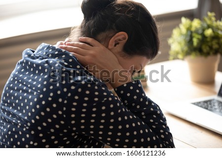 Fatigued indian woman student office worker massage sore neck stiff muscles tired from computer work at desk on bad chair in incorrect position feel back pain ache concept, closeup over shoulder view