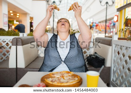 Fatty woman eating pizza, unhealthy food #1456484003
