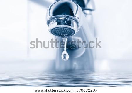 Faucet and water drop close up