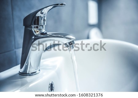 Faucet and water drop close up. Bathroom interior with sink and water tap. Foto d'archivio ©