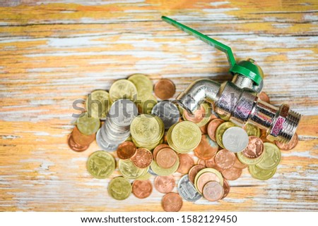 faucet on money coin wood background , top view / water savings and faucet money fall concept Foto d'archivio ©