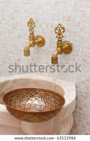 faucets and  copper bowl in turkish bath. water flowing