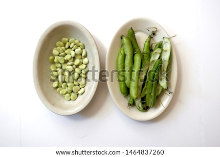 fava beans in their pods, piled in a vintage English ironstone dish, beside a vintage English ironstone platter of fava bean pods set atop a white background, shot from above