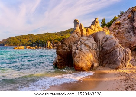 Fava sandy beach, Vourvourou, Chalkidiki or Halkidiki, Greece summer sunset scenery with turquoise sea, forest green mountains and rocks