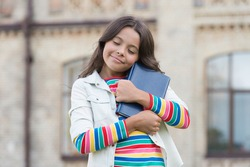 Favorite author. Being responsible for returning books on time can teach some basics of responsibility. Knowledge concept. Little girl hold book. Girl with book urban background. Book from library.