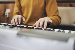 Favorite classical music Soft focus view of man hands playing a melody on piano while taking piano lessons. Musical instrument.  Piano keyboard