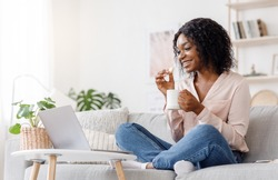 Favorite Pastime. Young Black Girl Relaxing At Home With Laptop And Tea, Watching Movies And Eating Crispy Waffles, Side View With Copy Space