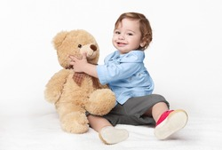 Favorite toy. Happy toddler boy playing with his teddy bear, studio shot, panorama