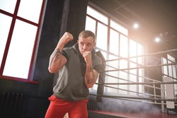 Favourite uppercut punch. Confident handsome athlete in sports clothing throwing uppercut opposite boxing ring