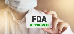 FDA Approved words on card Doctor shows. Food and Drugs Association approved products concept.