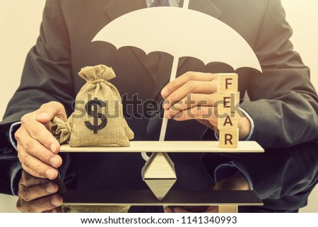 Fear and greed or anxiety in financial market concept : Businessman carries a white umbrella, protects dollar bags or properties on basic balance scale, depicts the influence of emotions on investors
