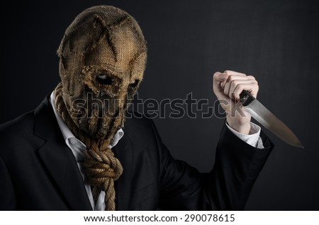 Fear and Halloween theme: a brutal killer in a mask holding a knife on a dark background in the studio