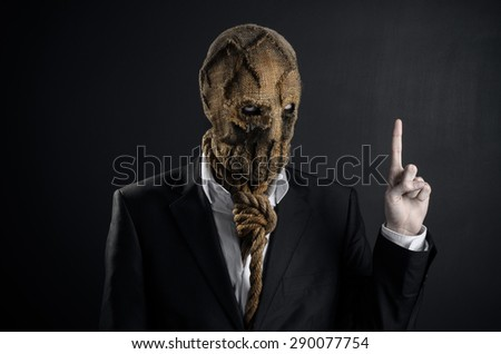 Fear and Halloween Theme: creepy killer in a mask on a dark background in the studio