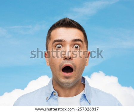 fear, emotions, horror and people concept - scared man shouting over blue sky and cloud background