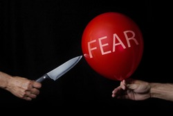 Fear. Getting rid of fears. Overcoming fear. Solution of problems. The knife pierces the red balloon.